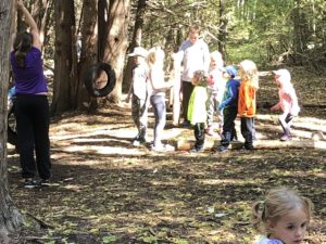 older children helping younger children use tire swing in forest