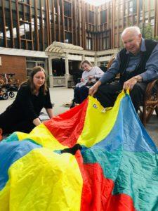 senior helping with children's parachute