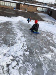 children sliding down sheer ice hill