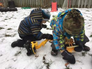 children digging for worms in snowy earth with digger toys