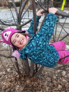 Child dangling from tree branch with big smile