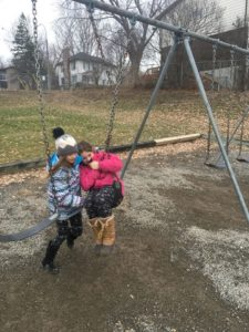 Two children on swings leaning into each other